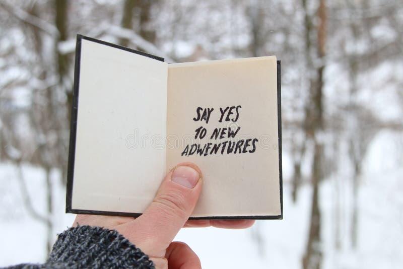 同意在拿着与题字的冬天森林手的背景的新的冒险一本书 库存图片
