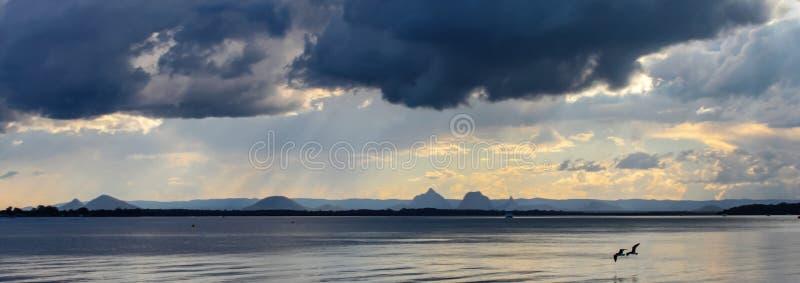 同时两只鸟在遥远的山- bann飞行在水在与打破金黄的太阳的不祥的黑暗的云彩下并且下雨 免版税库存图片