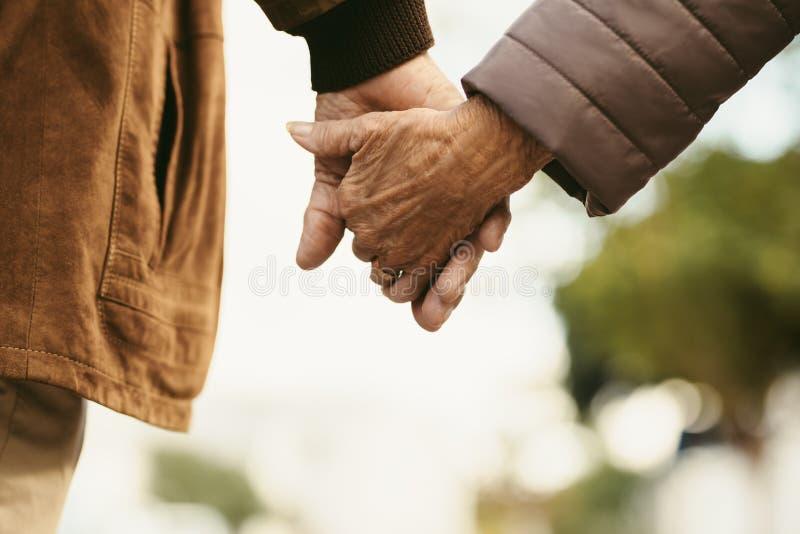 同时永远-手拉手走老的夫妇 库存图片