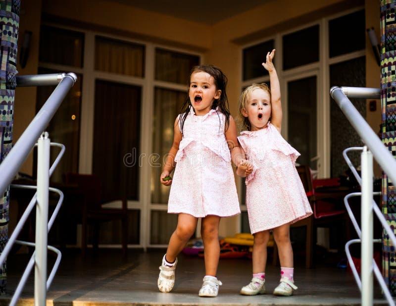同样的两个姐妹女婴穿戴,握手 免版税图库摄影