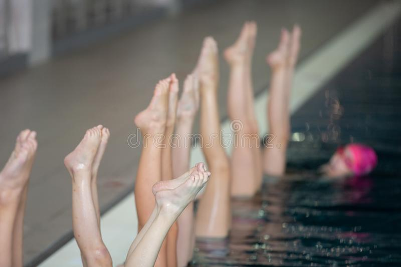 同步的游泳者指向在行动的水外面 同步的游泳者腿运动 花样游泳队 免版税图库摄影