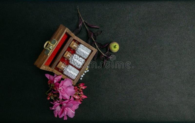 同种疗法有黄柏的药瓶顶视图在木经典箱子和新鲜的狂放的桃红色花与疏散小球在黑暗 图库摄影