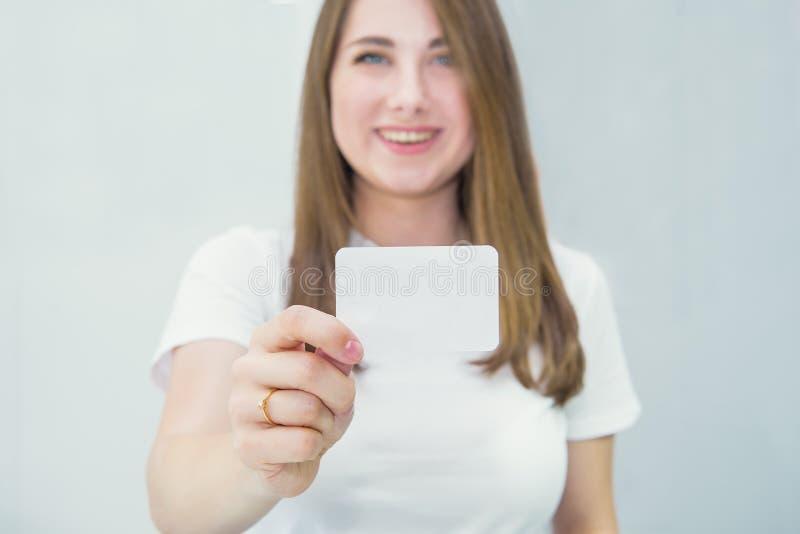 名片或礼品券 显示被聚焦的空白的空的纸牌的便服的被弄脏的愉快和激动的白种人妇女 免版税图库摄影