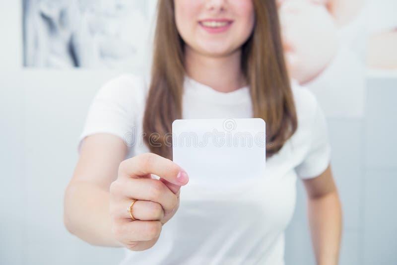 名片或礼品券 显示被聚焦的空白的空的纸牌的便服的被弄脏的愉快和激动的白种人妇女 库存照片