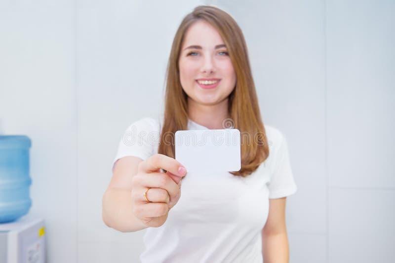 名片或礼品券 显示被聚焦的空白的空的纸牌的便服的被弄脏的愉快和激动的白种人妇女 库存图片
