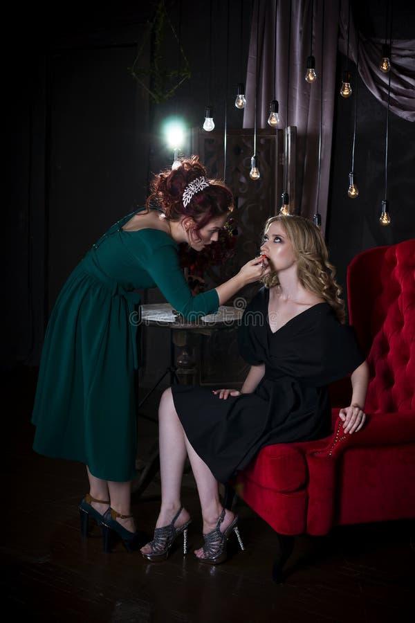 后台场面:化妆师在photoshoot前应用唇膏,美丽的妇女面孔,完善的构成 图库摄影