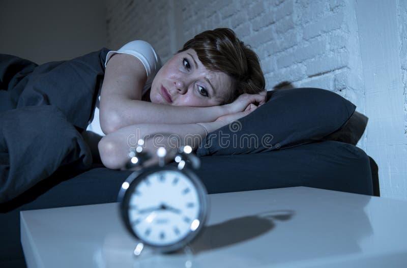 后在床上的年轻美丽的妇女在遭受失眠的晚上设法睡觉 免版税库存图片