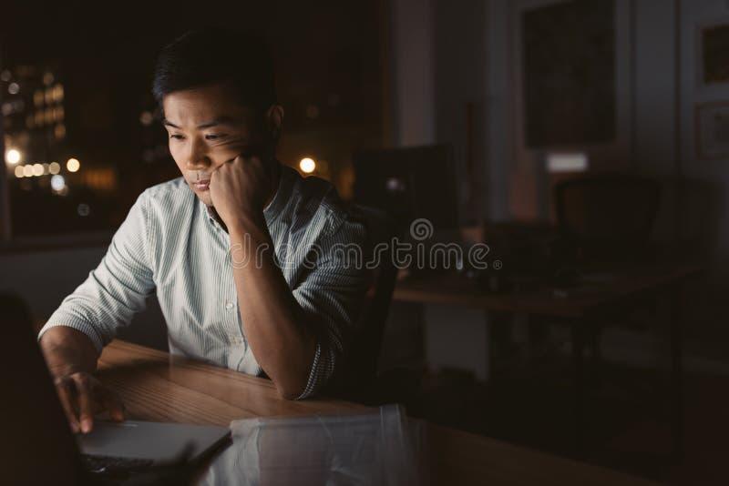 后工作在他的书桌的疲乏的亚洲商人在晚上 库存图片