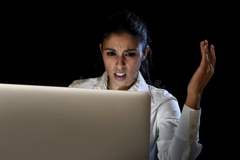 后工作在便携式计算机上的黑暗中的妇女在震动和重音惊奇的晚上 库存图片