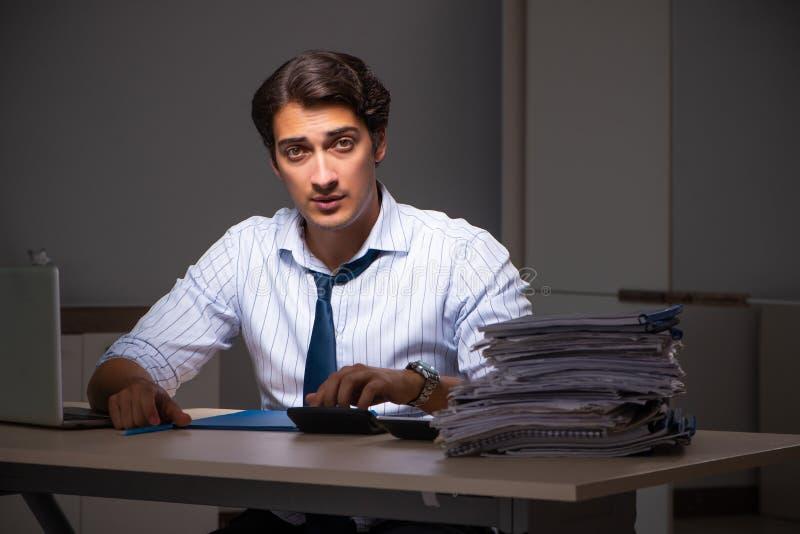 后工作在晚上的年轻财政经理在办公室 免版税库存图片