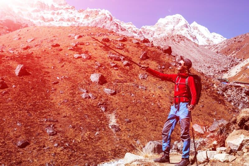今后指向用拐棍的年轻男性山远足者 免版税库存图片