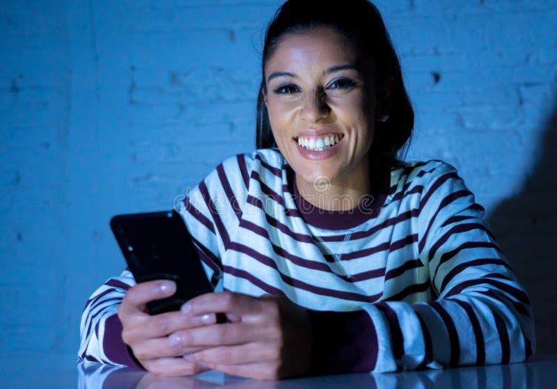 后挥动和聊天在她巧妙的电话的年轻美丽的妇女在晚上 免版税库存照片