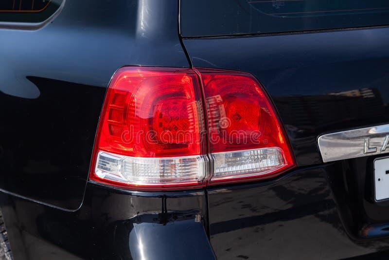 后方尾灯视图在黑色的丰田陆地巡洋舰200在清洗在销售前以后在停车处的一好日子 库存图片