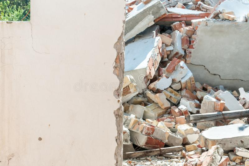 后果保持有残破和损坏的屋顶的老倒塌的房子有砖墙的在灾害以后 免版税库存图片