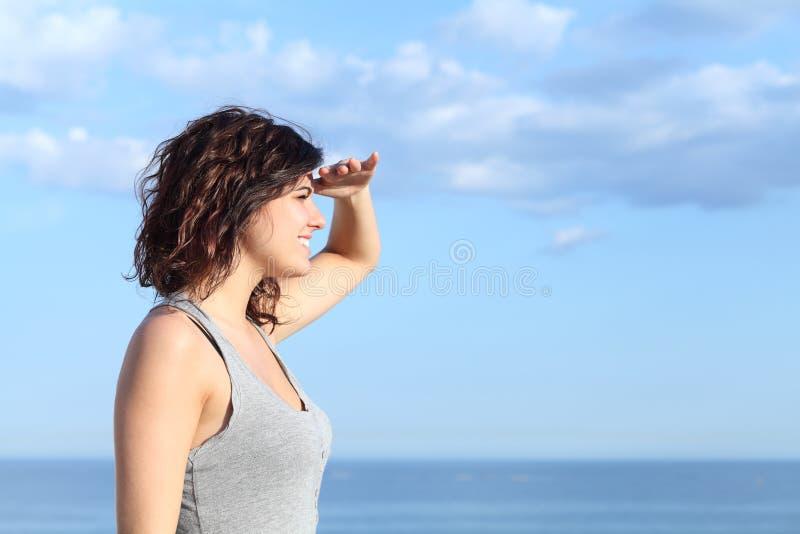今后看用在前额的手的美丽的妇女 免版税库存图片