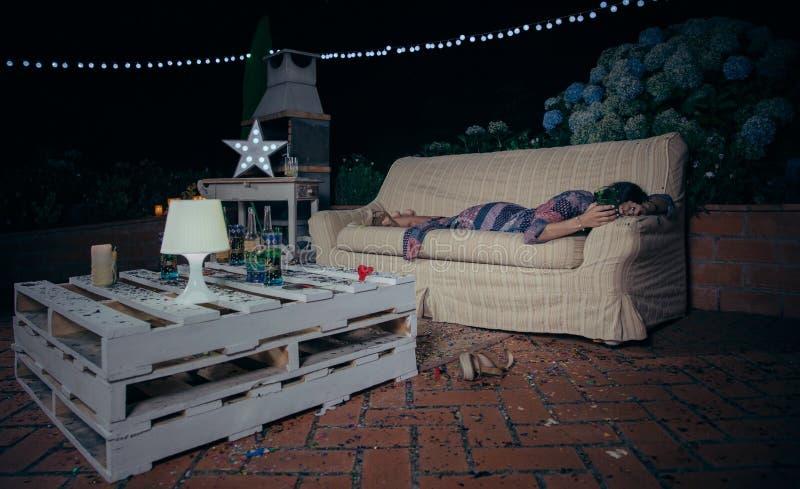 以后睡觉在沙发的孤独的被喝的妇女 免版税库存照片