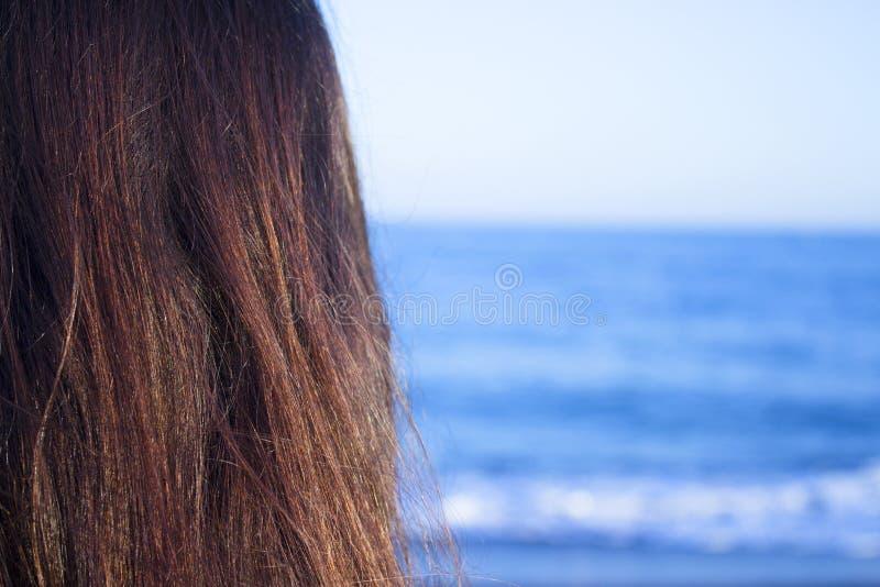 后背有女人头朝的海滩美景 免版税图库摄影