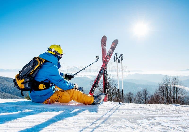 后视图射击了滑雪者坐雪在采取与他的行动照相机的山顶部selfies 免版税图库摄影