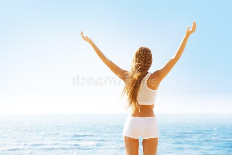 后视女人后视,天海景中举起双臂,白衣少女 免版税库存照片