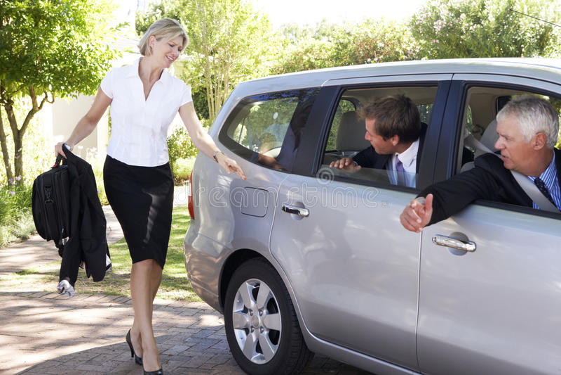 后跑的女实业家遇见合并旅途的同事汽车入工作 免版税库存照片