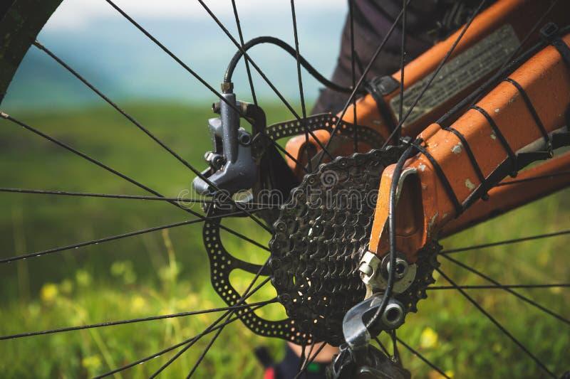 后轮卡式磁带特写镜头视图从登山车的在风景和绿草 库存图片