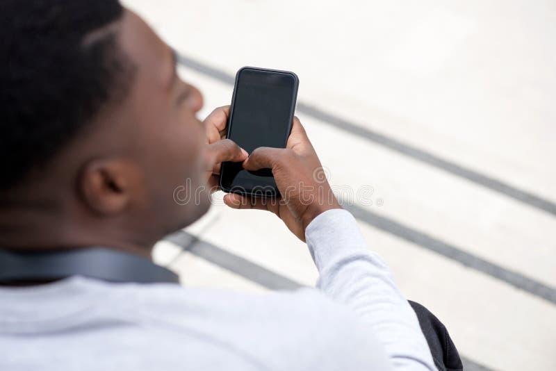 后边年轻黑人藏品智能手机 库存照片