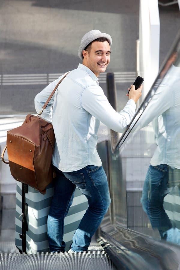后边自动扶梯的旅行人与手提箱袋子和手机 免版税图库摄影