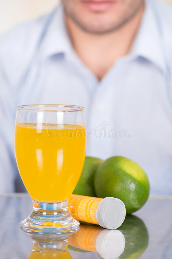 后边英俊的人维生素C柠檬、药片和一杯维生素C溶化了在桌 免版税图库摄影