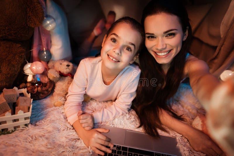 后采取selfie的母亲和女儿在枕头房子里在晚上在家 图库摄影