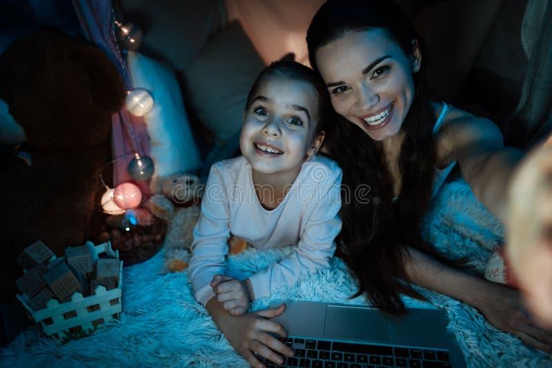 后采取selfie的母亲和女儿在枕头房子里在晚上在家 库存照片