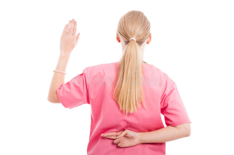 后面做假誓言姿态的看法医疗女性护士 免版税图库摄影
