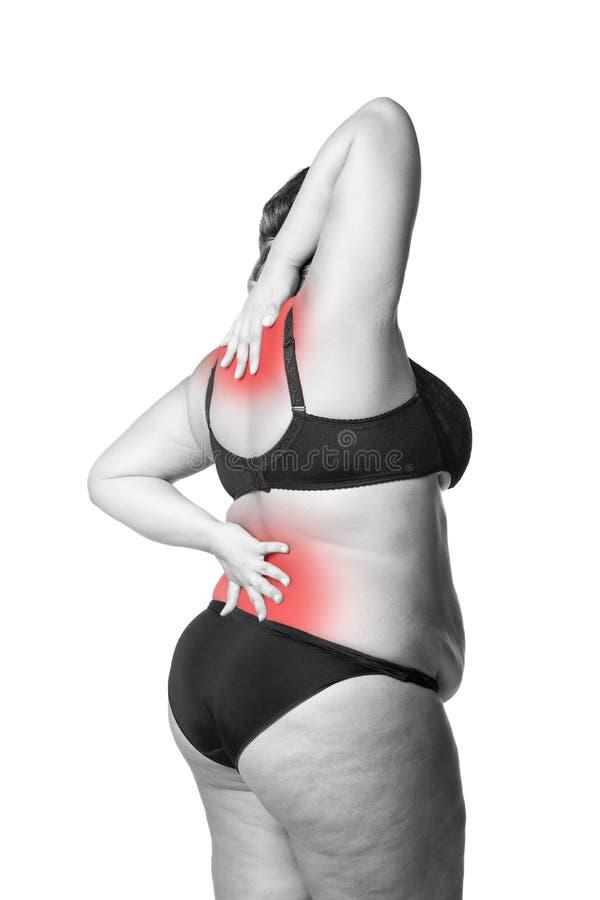 后面和脖子痛,肥胖妇女以腰疼,在白色背景隔绝的超重女性身体 库存照片