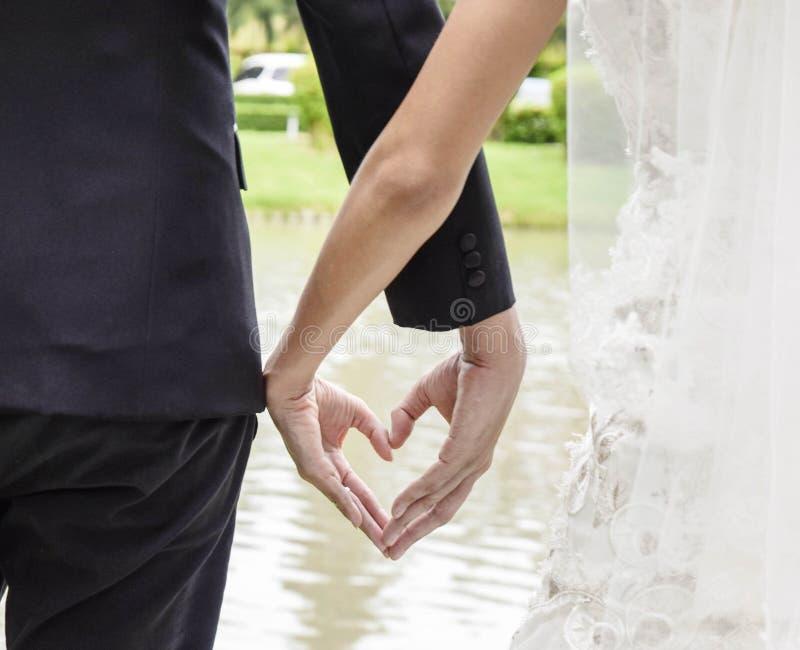 后面拿着手心脏的衣服的观点的白色礼服的新娘和新郎塑造认真地婚姻的题材 图库摄影