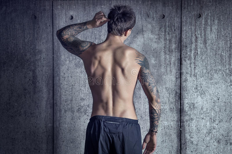 从后面的体育适合的肌肉被刺字的人在顶楼空间 免版税图库摄影