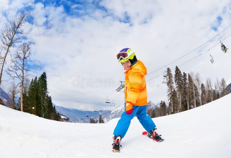 从后面的男孩佩带的滑雪帽滑雪视图 库存图片