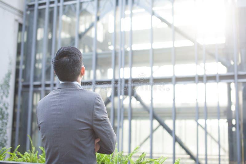 从后面的看的玻璃大厦的雄心勃勃的商人 库存照片