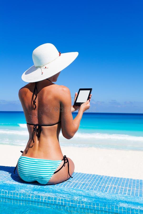 从后面的美丽的妇女读与帽子的ebook 免版税库存图片