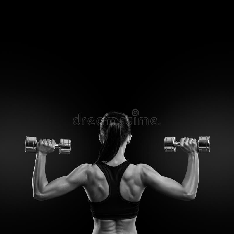后面的训练肌肉的健身妇女有哑铃的 免版税库存图片