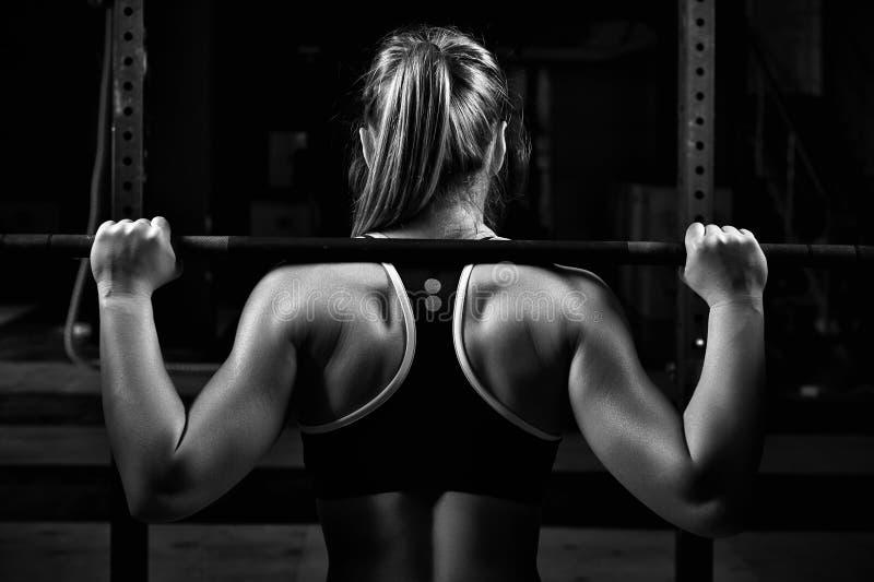 后面看法年轻女性做的杠铃在健身房蹲 免版税图库摄影
