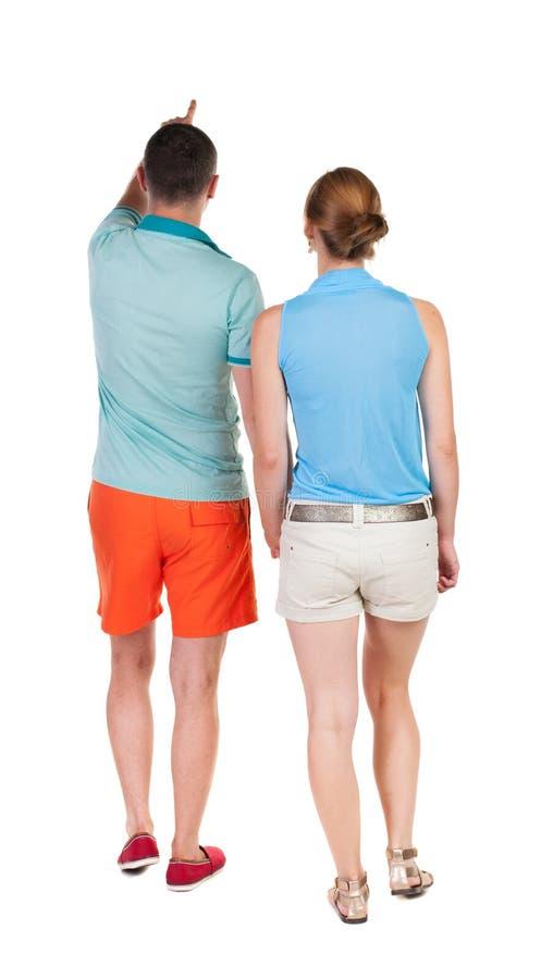 后面看法走的年轻夫妇(男人和妇女)指向 免版税库存图片