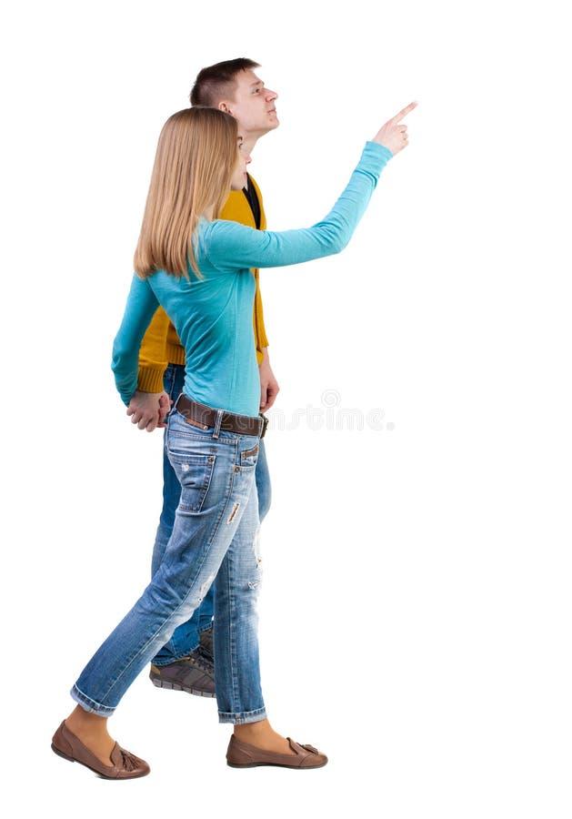 后面看法走的年轻夫妇(男人和妇女)指向 库存照片