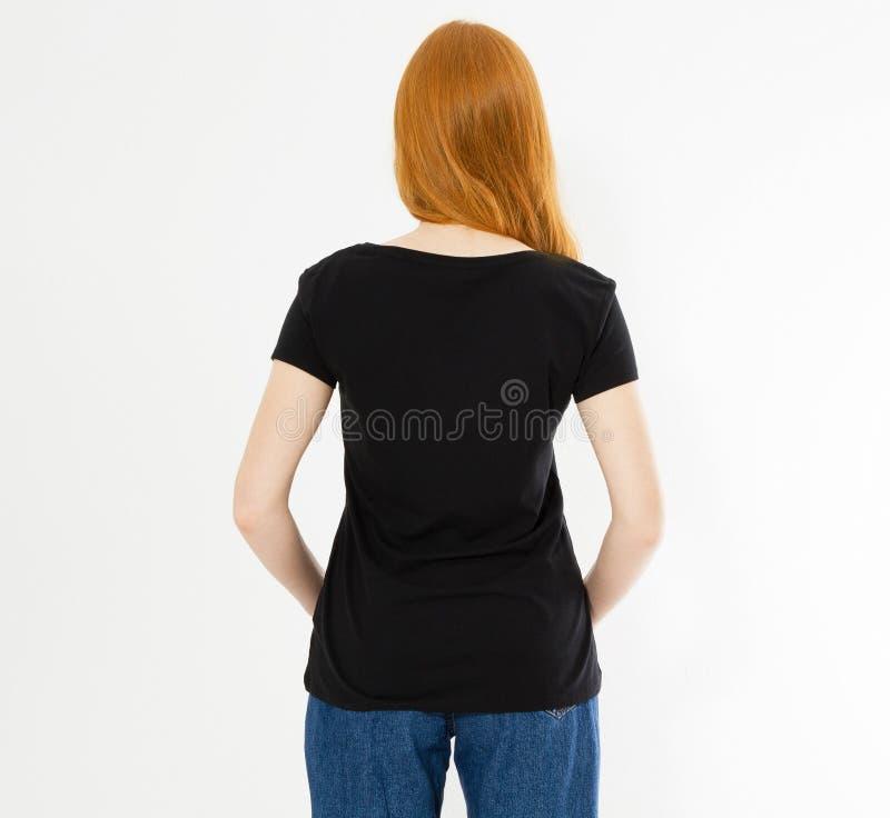 后面看法T恤杉设计,愉快的人概念-空白的黑T恤杉的微笑的红色头发妇女把她的手指指向的她自己, 库存照片