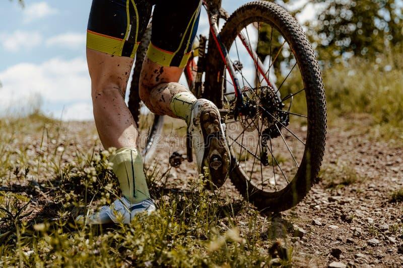 后面肮脏的脚山骑自行车的人 免版税库存照片