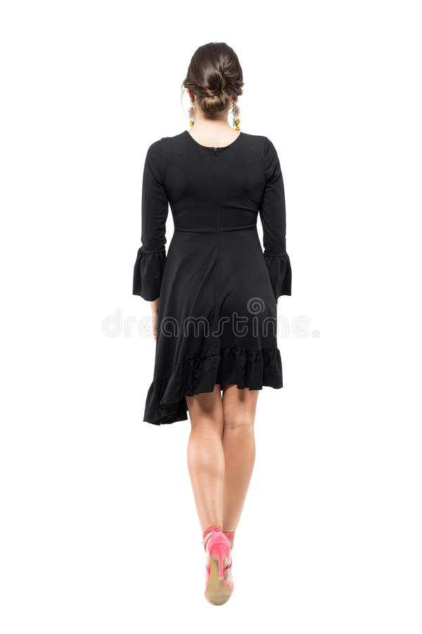 后面被装饰衣裙的观点的有小圆面包发型的少妇和黑色穿戴走开 免版税库存图片