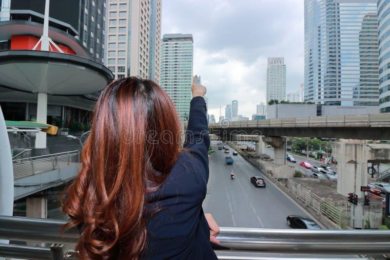 后面观点广角射击把手指指向的年轻亚裔女商人都市很远建立背景 库存图片
