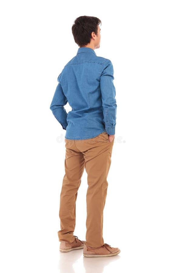后面观点的一个偶然人用在口袋的手 免版税库存图片