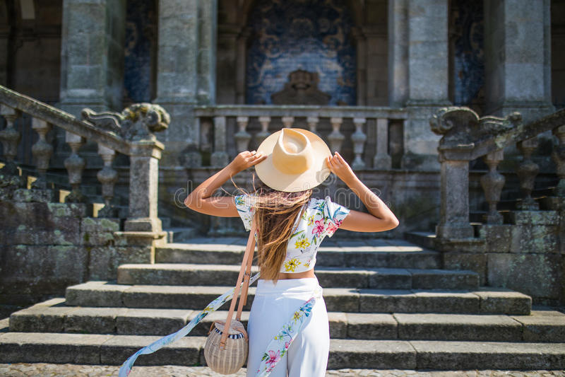 后面观点的一个时髦的女性游人敬佩一个美丽的建筑大厦在走期间在外国城市,少妇tr 免版税库存图片