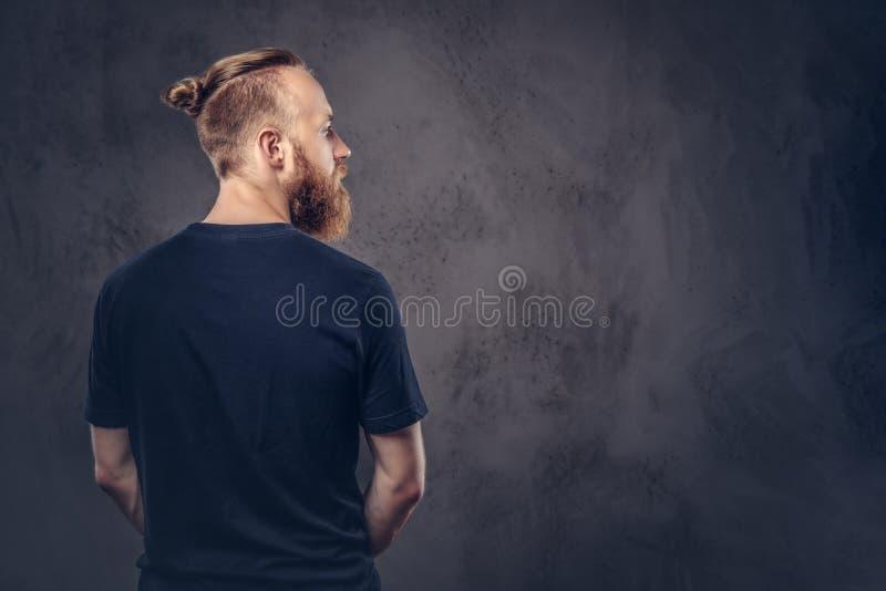 后面观点的一个红头发人有胡子的人在一件黑T恤杉穿戴了 隔绝在黑暗的织地不很细背景 库存照片