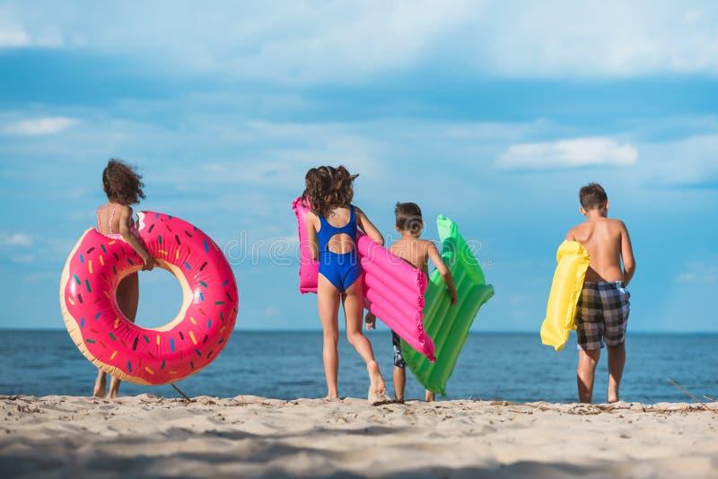 后面观点的与可膨胀的床垫的孩子走在海滩的小组  图库摄影