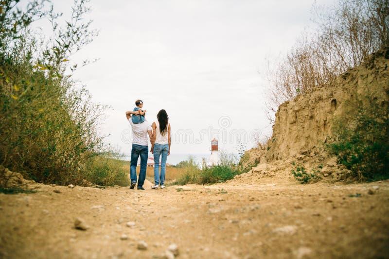 后面观点的与走到白色灯塔的一个小孩子的年轻家庭,户外背景 免版税库存照片